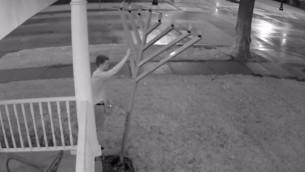 Une vidéo de sécurité montrant un homme frappant la hannoukia du Habad de l'université de l'Illinois, le 21 août 2015. (Crédit : capture d'écran YouTube)