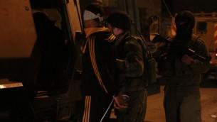 Des soldats faisant monter un Palestinien, qui est soupçonné d'avoir pris part à des manifestations violentes, à l'arrière d'un véhicule blindé à Qalqilya le 14 janvier 2016 (Crédit : Judah Ari Gross / Times of Israel)