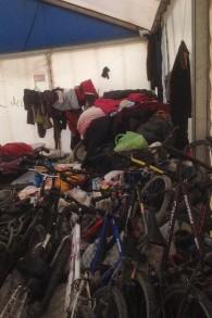 Les piles de vêtements et de vélos à l'intérieur de la tente soudanaise dans le camp de réfugiés de Calais, le 8 février 2016 (Crédit : Jenni Frazer / The Times of Israel)