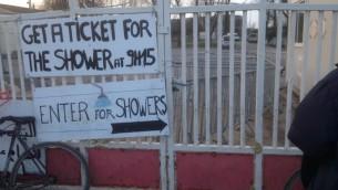 Un panneau montrant les douche gérées par les autorités françaises dans le camp de Calais. Chaque douche ne doit pas dépasser six minutes. Photographie prise le 8 février 2016. (Créidt : Jenni Frazer/Times of Israel)