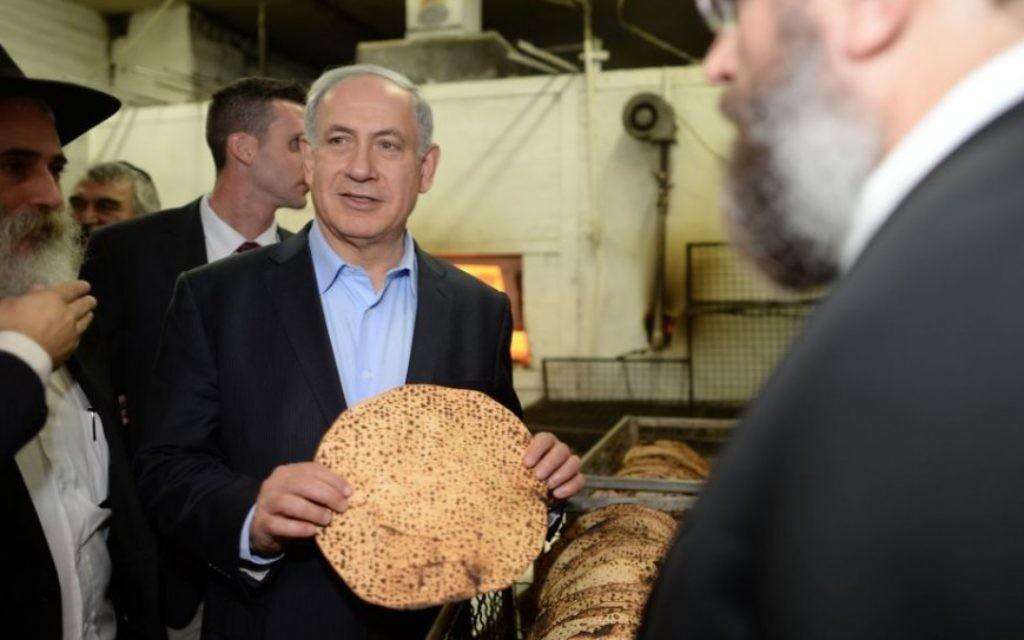 Le Premier ministre Benjamin Netanyahu avec une matzah shmoura dans une boulangerie de Kfar Chabad, en Israël, avant Pessah, le 1er avril 2014. (Crédit : Kobi Gideon/GPO/Flash90)