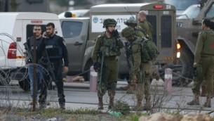 Les forces de sécurité israéliennes surveillent la zone où un Palestinien a tenté de poignarder des soldats israéliens avant d'être abattu à un checkpoint proche de Ramallah, en Cisjordanie, le 26 février 2016. (Crédit : AFP/Abbas Momani)