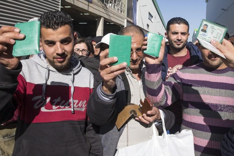 Les employés palestiniens de la firme israélienne Sodastream qui montrent leurs cartes d'identité palestiniennes avant de quitter l'usine de Rahat après avoir été licencié le 29 février 2016 (Crédit : AFP / JACK GUEZ)