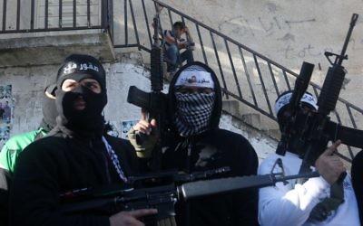 Les membres palestiniens des brigades des martyrs d'Al-Aqsa, la branche armée du mouvement Fatah, levant leurs armes lors d'un rassemblement pour soutenir le président de l'Autorité palestinienne Mahmoud Abbas et son gouvernement le 1er mars, 2016, dans le camp de réfugiés de Cisjordanie à Balata près de Naplouse ( Crédit : AFP/JAAFAR ASHTIYEH)