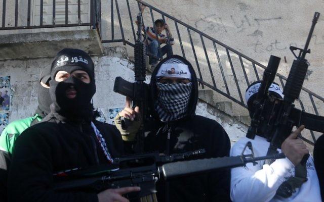 Illustration : des membres palestiniens des Brigades des martyrs d'Al-Aqsa, l'aile terroriste du Fatah, lèvent les armes lors d'un rassemblement en soutien au président de l'Autorité palestinienne, Mahmoud Abbas, et à son gouvernement, le 1er mars 2016, dans le camp de réfugiés de Balata, en Cisjordanie, près de Naplouse. (Crédit : AFP / Jaafar Ashtiyeh)