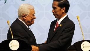 Le président de l'Indonésie Joko Widodo (d) serre la main au président de l'Autorité palestinienne Mahmoud Abbas (g) lors de la clôture du 5e sommet de l'Organisation islamique de la coopération (OCI) sur les territoires palestiniens, le 7 mars 2016 à Jakarta. (Crédit : GARRY LOTULUNG / POOL / AFP)