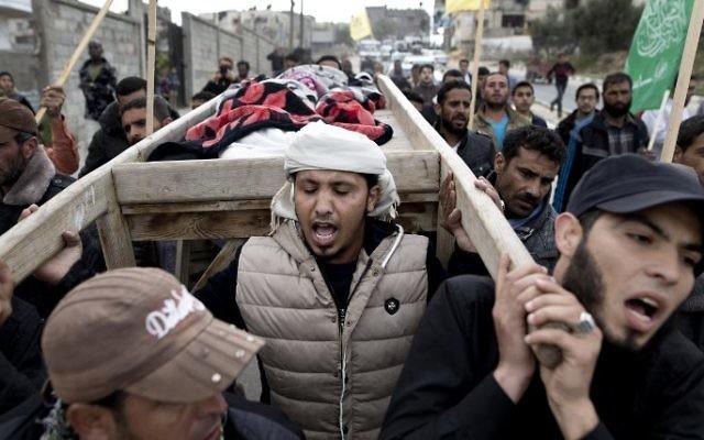 Les funérailles de deux enfants tués dans une frappe de représailles de l'armée israélienne suite à une salve de roquette tombée la veille au soir, le 12 mars 2016 à Beit Lahiya dans le nord de la bande de Gaza (Crédit : AFP / MAHMUD HAMS)