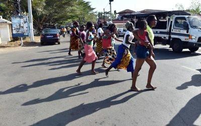 Les gens en train de fuir la plage après que des hommes lourdement armés ont ouvert le feu dans un hôtel dans la station balnéaire de Grand-Bassam en Côte d'Ivoire, le 13 mars 2016 (Crédit : AFP / ISSOUF SANOGO)
