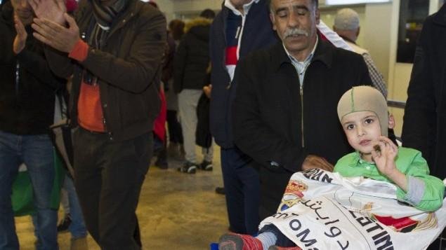 Le petit garçon palestinien de cinq ans, Ahmed Dawabsha (au centre), qui a survécu à une attaque menée par des extrémistes juifs qui ont tué ses parents et son frère, arrivant à l'Aéroport Adolfo Suarez près de Madrid, le 16 mars 2016, avant de rencontrer les stars du Real Madrid, y compris son idole Cristiano Ronaldo (Crédit : AFP / CURTO DE LA TORRE)