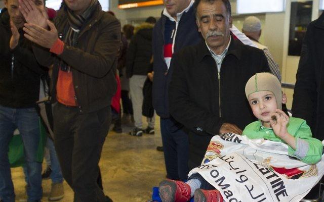 Ahmed Dawabsha, au centre, petit garçon palestinien de 5 ans qui a survécu à une attaque menée par des extrémistes juifs qui ont tué ses parents et son frère, à l'aéroport Adolfo Suarez près de Madrid, pour rencontrer les stars du Real Madrid, y compris son idole Cristiano Ronaldo, le 16 mars 2016. (Crédit : Curto de la Torre/AFP)