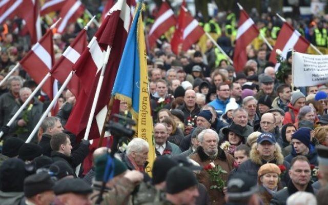 Des vétérans de la légion lettone, une force qui était commandée par les Waffen SS allemands nazis pendant la Seconde Guerre Mondiale, et leurs sympathisants portent des fleurs pendant leur marche vers le monument de la Liberté en Lettonie, à Riga, le 16 mars 2016. (Crédit : AFP/Ilmars Znotins)
