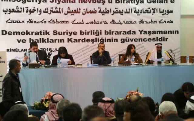 Aldar Khalil (C), du Mouvement pour une société démocratique, et le cheikh Hamad Sheikh Shihadeh (à droite), le chef du clan Naim dans le nord de la Syrie, lors d'une réunion de plus de 150 délégués kurdes, arabes, assyriens et d'autres parties dans la ville de Rmeilan, dans la province de Hasakah nord-est de la Syrie, où la décision a été prise d'établir une région fédérale, le 16 mars 2016 (Crédit : AFP / DELIL SOULEIMAN)
