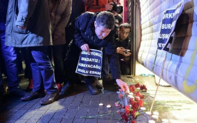 Un homme allume une bougie sur le site d'un attentat suicide dans la rue Istiklal, un quartier commerçant et touristique majeur, dans le centre d'Istanbul, le 19 mars 2016 (Crédit : AFP / BULENT KILIC)