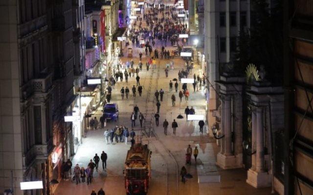 Les piétons marchent dans la rue Istiklal, située dans le centre d'Istanbul, le lendemain d'un attentat suicide, le 20 mars 2016. (Crédit : AFP / YASIN AKGUL)