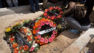 Une proche se recueille sur la tombe de Simha Damri, 60 ans, pendant ses funérailles à Dimona, dans le sud d'Israël, le 21 mars 2016. (Crédit : AFP / MENAHEM KAHANA)