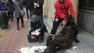 Un agent de sécurité privé aide une femme blessée devant la station de métro de Maalbeek, à Bruxelles, le 22 mars 2016, après une explosion dans la station proche des institutions européennes. (Crédit : AFP / Michael VILLA)