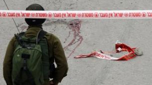 Un soldat de Tsahal se tient près des taches d'un Palestinien qui aurait reçu une balle dans la tête tirée par un soldat alors qu'il gisait blessé sur le sol après avoir poignardé et blessé un soldat israélien à Hébron le 24 mars 2016 (Crédit : AFP / Hazem Bader)