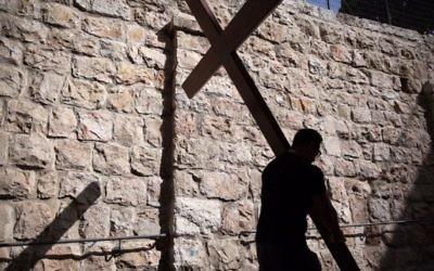 Un pèlerin catholique porte une croix de bois le long de la Via Dolorosa (chemin de la souffrance) dans la Vieille Ville de Jérusalem pendant la procession du Vendredi, le 25 mars 2016. (Crédit : Gali Tibbon / AFP)