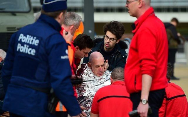 Une victime reçoit les premiers soins par les secouriste, le 22 mars 2016 à proximité de la station de métro Maelbeek à Bruxelles, après une explosion dans cette station qui se situe à proximité des institutions européennes (Crédit : AFP PHOTO / EMMANUEL DUNAND)