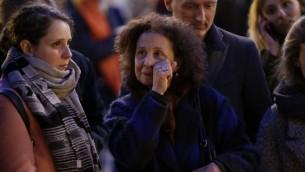 Une femme émue à un mémorial de fortune devant la Place de la Bourse (Beursplein) à Bruxelles le 22 mars 2016, suite aux attaques dans la capitale belge, qui a tué environ 31 personnes et blessé des centaines de personnes (Crédit : AFP PHOTO / KENZO TRIBOUILLARD)