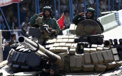 Des soldats iraniens saluent depuis un tank pendant la parade militaire annuel marquant l'anniversaire de la guerre de l'Iran contre l'Irak (1980 - 1988) à Téhéran, le 22 septembre 2014. (Crédit : Behrouz Mehri/AFP)