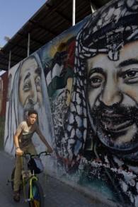 Un garçon palestinien sur son vélo passant devant une fresque dépeignant des graffitis (de gauche à droite) du regretté fondateur du Front Populaire pour la Libération de la Palestine (FPLP) Georges Habache, le chef spirituel du Hamas, le cheikh Ahmed Yassine et le dirigeant palestinien défunt Yasser Arafat, le 21 novembre 2014 dans la ville de Gaza (Crédit : AFP / MOHAMMED ABED)