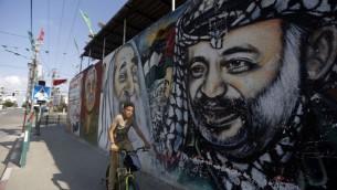 Un garçon palestinien sur son vélo passant devant une fresque dépeignant des graffitis (de gauche à droite) du fondateur du Front Populaire pour la Libération de la Palestine (FPLP) Georges Habache, le chef spirituel du Hamas, le cheikh Ahmed Yassine et le dirigeant palestinien défunt Yasser Arafat, le 21 novembre 2014 dans la ville de Gaza (Crédit : AFP / MOHAMMED ABED)