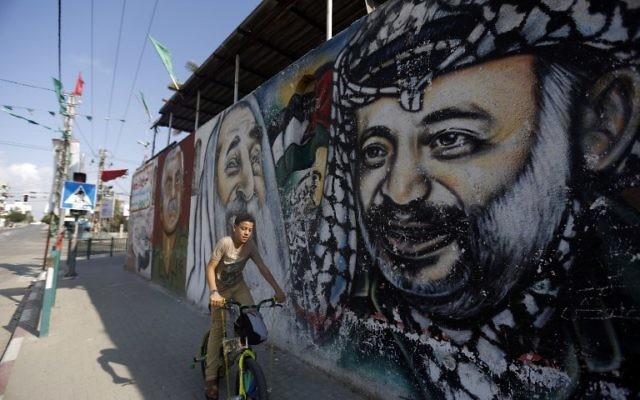 Un garçon palestinien sur son vélo passant devant une fresque de graffitis représentant (de gauche à droite) le fondateur du Front Populaire pour la Libération de la Palestine (FPLP) Georges Habache, le chef spirituel du Hamas, le cheikh Ahmed Yassine et le dirigeant palestinien défunt Yasser Arafat, le 21 novembre 2014 dans la ville de Gaza. (Crédit : AFP / MOHAMMED ABED)