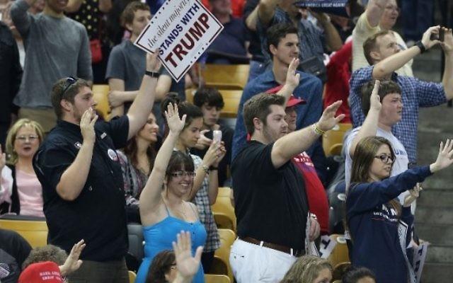 Le public lève le bras droit comme l'a demandé le candidat républicain Donald Trump pour promettre qu'ils voteront pour lui, pendant un évènement de campagne au CFE Arena, sur le campus de l'université de Floride, à Orlando, le 5 mars 2016. (Crédit : Joe Raedle/Getty Images/AFP)