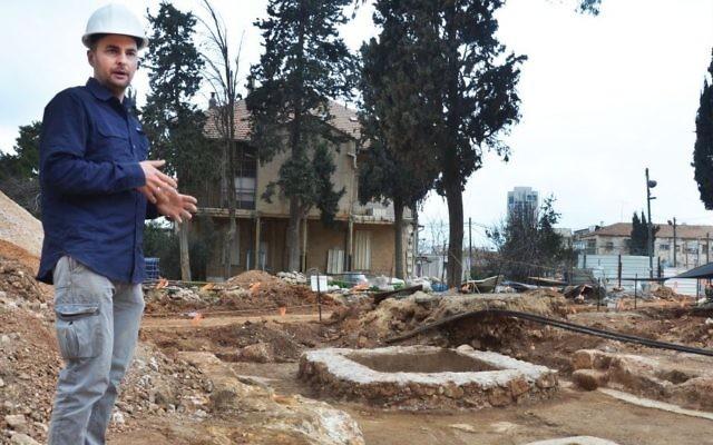 Le directeur de la fouille, Alex Wiegmann, aux côtés d'un ancien complexe découvert sur le site de l'ancienne base Schneller de Tsahal à Jérusalem. (Crédit : Israel Antiquities Authority)