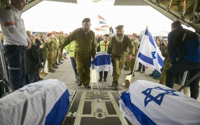 Des soldats israéliens en train de charger des cercueils transportant les corps des Israéliens tués dans un attentat suicide la veille à Istanbul dans un avion de Tsahal, le 20 mars 2016. (Crédit : unité des porte-paroles de l'armée israélienne)