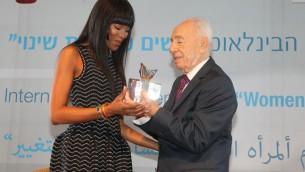 """L'ancien président de l'Etat d'Israël Shimon Peres (à droite) a remis une récompense à la top-modèle Naomi Campbell au Centre Peres pour la Paix, pendant l'évènement """"Les femmes menant le changement """" tenu à l'occasion de la journée internationale des droits des femmes, à Tel Aviv, le 8 mars 2016. (Crédit : Rafi Daloya)"""