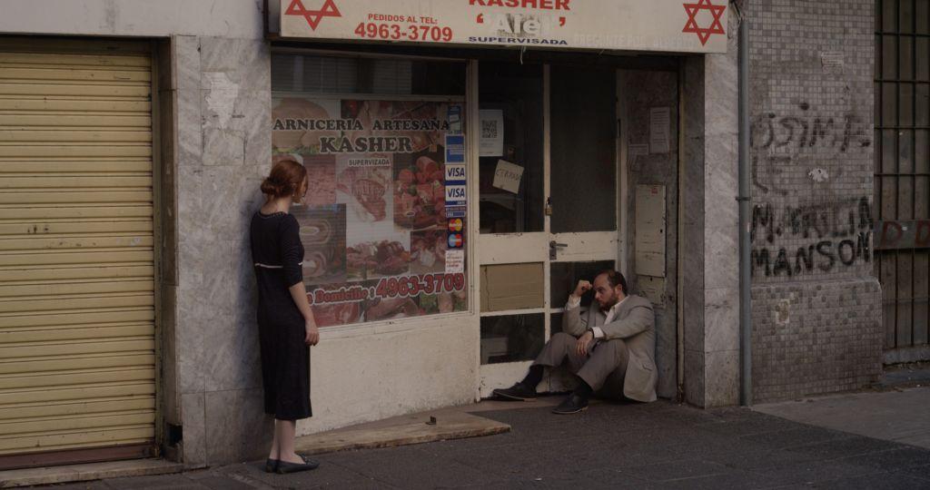 Une scène de Daniel Burman 'The Tenth Man', les acteurs Alan Sabbagh et Julieta Zylberberg devant une boucherie casher (Crédit : Autorisation)