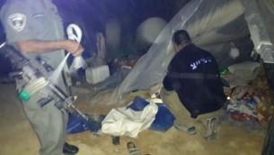 Des policiers collectent des preuves et démantèlent les logements de fortune d'un groupe de 22 Palestiniens qui vivaient illégalement en Israël, près du parc national Besor Stream, le 10 mars 2016. (Crédit : police israélienne)