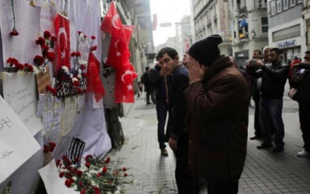Un homme ému devant un mémorial improvisé à l'emplacement de l'explosion d'un attentat suicide dans la rue Istiklal, un quartier commerçant et touristique majeur, dans le centre d'Istanbul, le 20 mars 2016. (Crédit : AFP / Yasin Akgul)