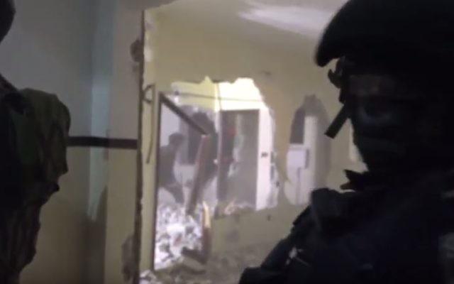 Des officiers de la police des frontières et des soldats ferment l'appartement d'un terroriste palestinien à Hébron, le 8 mars 2016. (Crédit : capture d'écran YouTube/Judah Ari Gross)
