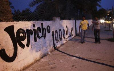 Des Palestiniens passant devant un mur peint en l'honneur des 10 000 ans de la ville de Jéricho en Cisjordanie (Crédit : Miriam Alster / FLASH90)