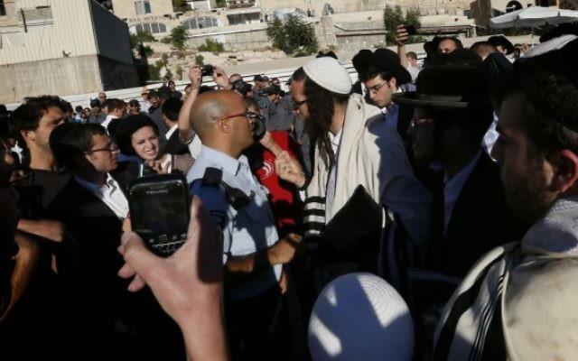Des hommes juifs orthodoxes utilisent des sifflets pour tenter de perturber le service de prières mensuel des Femmes du mur, au mur Occidental, le 7 août 2013. (Crédit : Miriam Alster/Flash90)