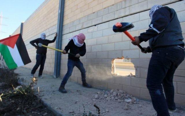 Des Palestiniens cassant la barrière de sécurité dans la ville de Bir Nabala, entre Jérusalem et Ramallah, en Cisjordanie, le 8 novembre 2014. (Crédit : STR/Flash90)