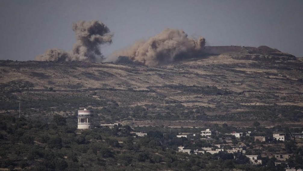 Les explosions dues aux combats en Syrie sont visibles depuis le côté israélien de la frontière, sur le plateau du Golan, le 16 juin 2015. (Crédit : Basel Awidat/Flash90)