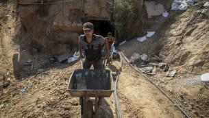 Des Palestiniens travaillant à l'entrée d'un tunnel utilisé pour passer des produits en contrebande entre l'Egypte et la bande de Gaza après avoir été inondée avec de l'eau de mer par l'armée égyptienne, à Rafah dans le sud de la bande de Gaza le 1er octobre 2015 (Crédit : Abed Rahim Khatib / Flash90)