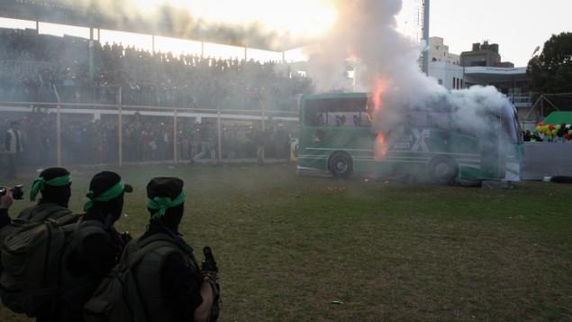 Des Brigades Izz ad-Din al-Qassam, la branche armée du Hamas, brûlant un faux bus israélien pendant un rassemblement anti-Israël à Rafah, dans le sud de la bande de Gaza, le 26 février 2016. (Crédit : Abed Rahim Khatib/Flash90)