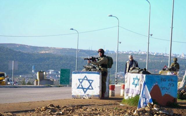 Un soldat des forces de sécurité israélienne près de la scène d'une attaque terroriste près de l'intersection de Gush Etzion en Cisjordanie le 4 mars 2016 (Crédit : Gershon Elinson / Flash90)