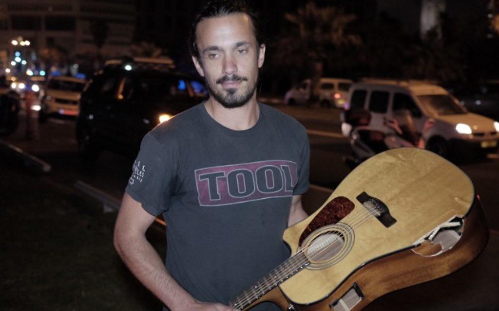 Yishay Montgomery tient la guitare endommagée qu'il a utilisée pour frapper Bashar Massalha lors de l'attaque terroriste à Jaffa le 8 mars 2016 (Crédit : Tomer Neuberg / Flash90)