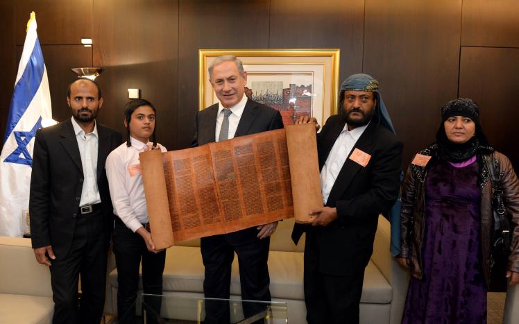 Le Premier ministre Benjamin Netanyahu avec un rouleau de Torah de plus de 500 ans avec certains des juifs yéménites qui sont arrivés en Israël dans le cadre d'une opération de sauvetage secrète, le 21 mars 2016. (Crédit : Haim Zach/GPO)