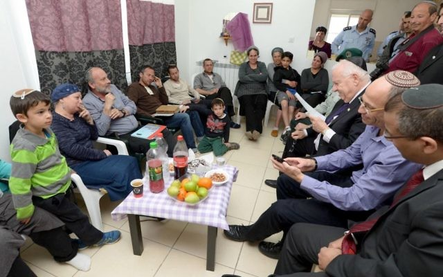 Le président Reuven Rivlin lors d'une visite de condoléances à la famille endeuillée de l'officier réserviste Eliav Gelman le 29 février 2016 (Crédit  : Mark Neiman / GPO)