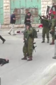 Un soldat israélien chargeant son arme avant de sembler tirer à la tête sur un assaillant palestinien au sol, apparemment désarmé, à la suite d'une attaque au couteau à Hébron, le 24 mars 2016. (Crédit : capture d'écran B'TSelem)