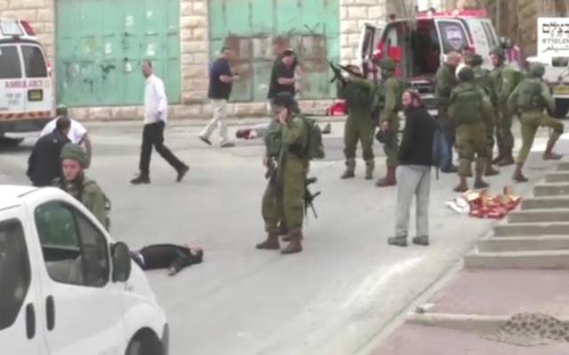 Un soldat israélien chargeant son arme avant de sembler tirer à la tête sur un terroriste palestinien au sol, apparemment désarmé, à la suite d'une attaque au couteau à Hébron, le 24 mars 2016. (Crédit: capture d'écran B'TSelem)