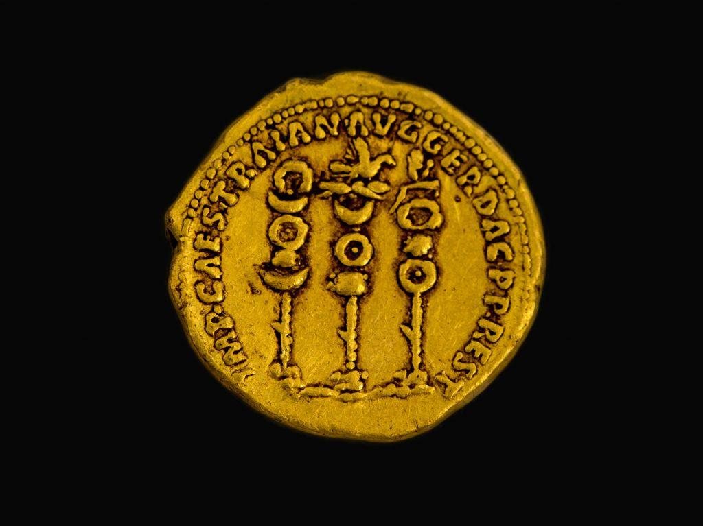 Les symboles des légions romaines à côté du nom du dirigeant Trajan sur une ancienne pièce d'or vieille de 2 000 ans trouvée dans le nord d'Israël (Crédit : Samuel Magal/Autorité de l'Autorité des Antiquités d'Israël)