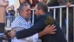 """Le père de Raed Jaradat et le père de Daania Arshid s'embrassent après avoir """"fiancé"""" leurs enfants morts l'un à l'autre pour être mariés l'un à l'autre comme """"martyrs"""" au paradis, le 31 octobre 2015. (Crédit : capture d'écran YouTube)"""